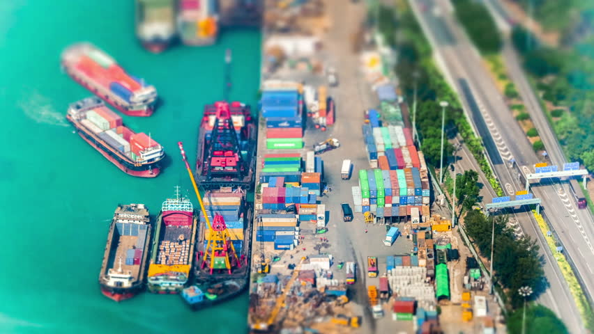 HONG KONG - JAN 23, 2015: Cargo ships loaded by crane with cargo containers at a busy port terminal. Hong Kong. Time lapse form aerial view point