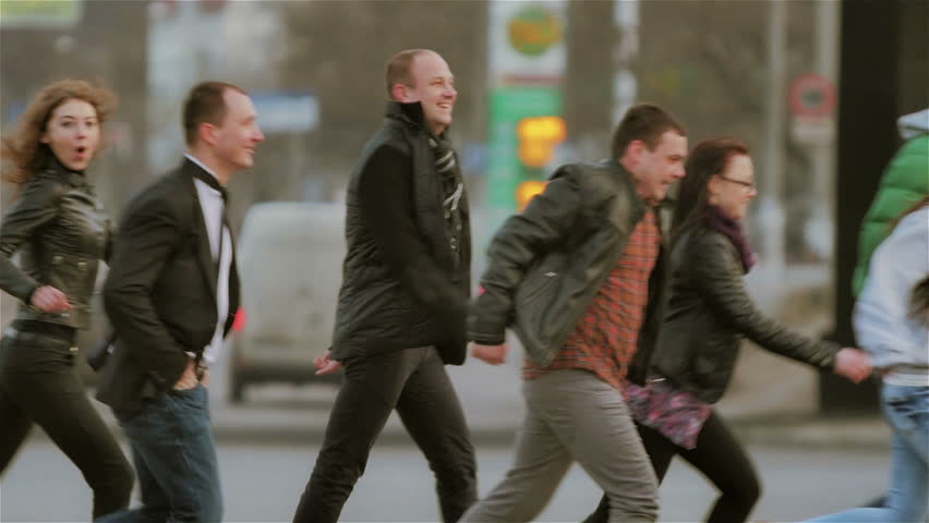 A group of young, active, cheerful people crossing the road. They run, laugh and rejoice in the background you can see the car traffic