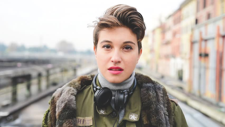 young beautiful short hair hipster woman in town smiling looking camera