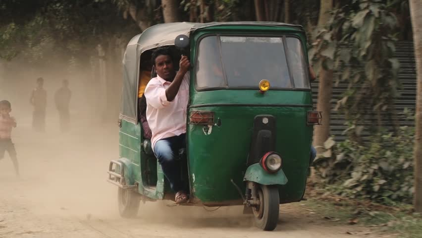 TANGAIL, BANGLADESH - FEBRUARY 14, 2014: Unidentified people ride a three-wheeler by a dusty countryside road on February 14, 2014 in Tangail, Bangladesh. #9417521