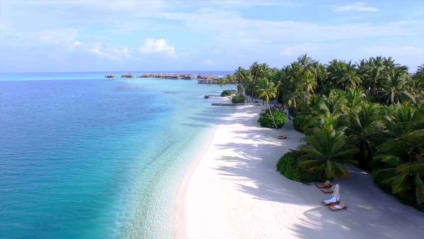 AERIAL: Luxury island resort on exotic white sand beach Royalty-Free Stock Footage #9426038