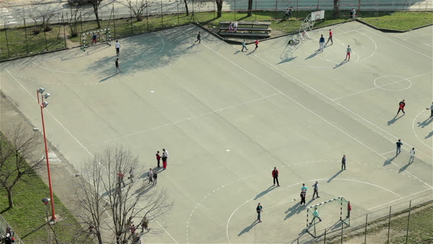 Group of children playing game with ball on school playground. Boys playing football and basketball on sport court. Kids training on school yard. Recreation,leisure time,soccer,sunny day,high angle. | Shutterstock HD Video #9442436