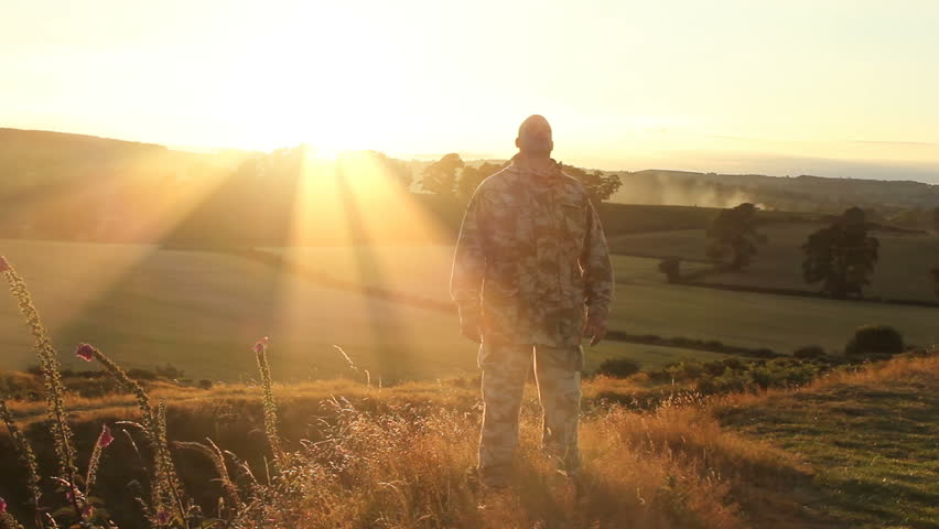 A soldier trying to forget the horror of war finds peace and solitude on top of a natural beauty spot as the sun is setting behind him. | Shutterstock HD Video #9444959