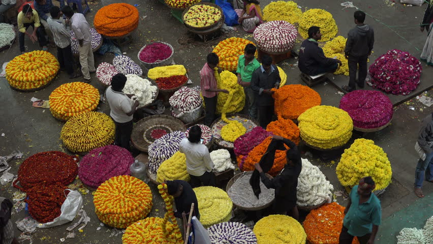 BANGALORE, INDIA - 18 NOVEMBER 2014: People buy and sell flowers at the colorful KR Flower Market in Bangalore.