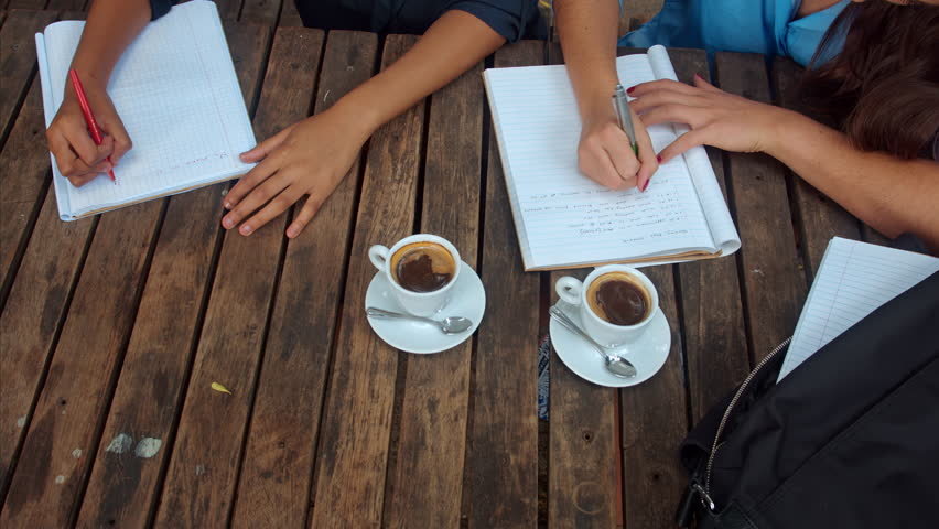 Above angle view of casual entrepreneur woman team/student team, writing down the brainstorming session, wile in a coffee meeting at cafe. | Shutterstock HD Video #9476126