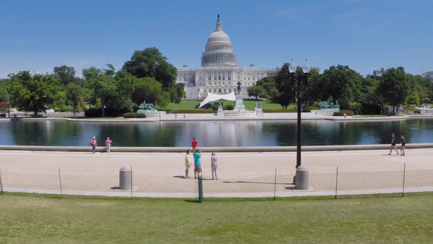 WASHINGTON - AUG 26, 2014: People walk near Capitol Reflecting Pool, Ulysses S. Grant Memorial and United States Capitol at summer day. Aerial view. Ulysses S. Grant was  the 18th President of US.