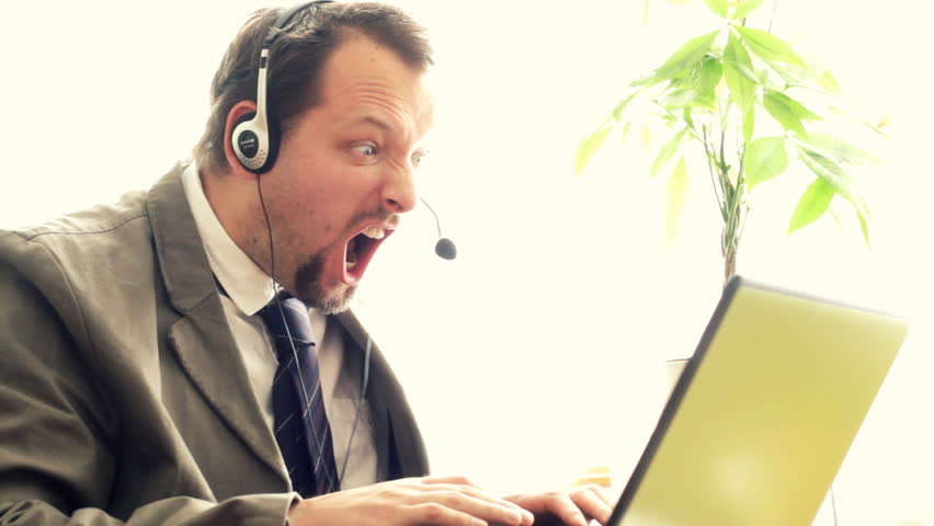 Angry man with headphones screaming at laptop