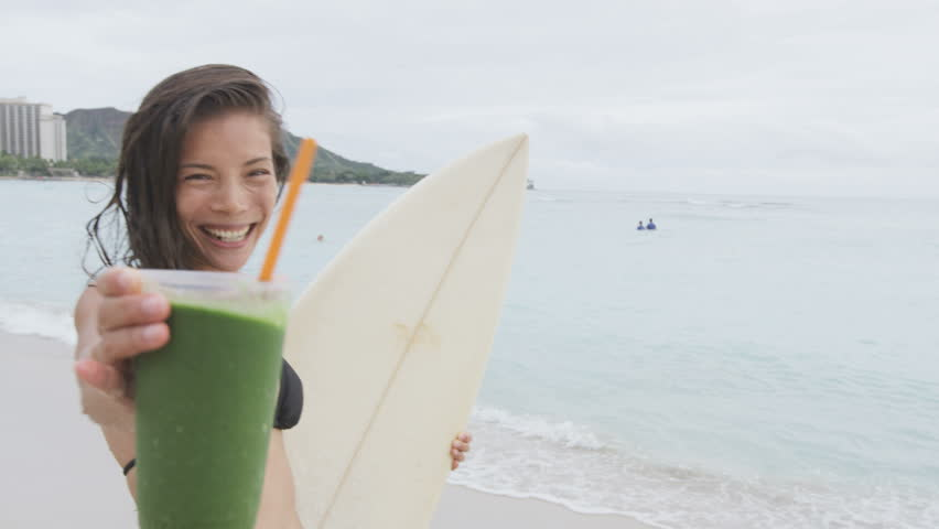 Healthy food and fitness lifestyle woman on beach drinking Green detox vegetable smoothie after surfing workout on summer day on beach. Healthy lifestyle concept with beautiful surfer model. 96 FPS.