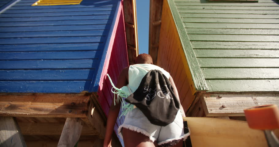 Cool African American girl longboarder walking through colourful beachhouse at the beach in Slow Motion