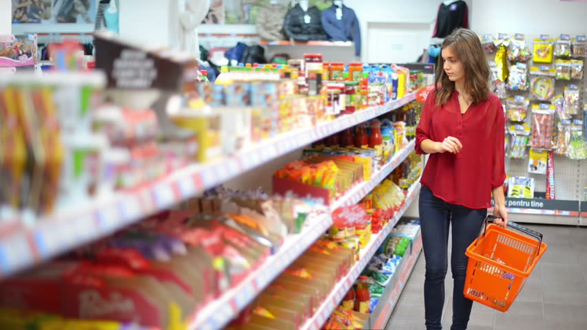 Happy woman with shopping basket choosing products in supermarket | Shutterstock HD Video #9535460