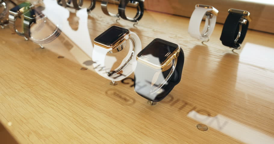 PARIS, FRANCE – APR 10, 2015: New wearable computer Apple Watch smartwatch Edition gold collection: 18-Karat Yellow Gold Case with White and black Sport Band with the price tag of 12000 USD