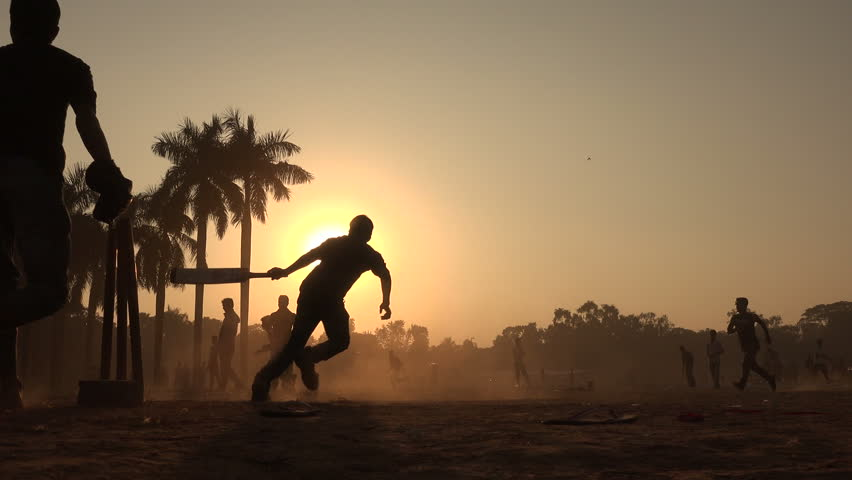 Silhouettes of young men playing cricket in a park in Dhaka, Bangladesh.