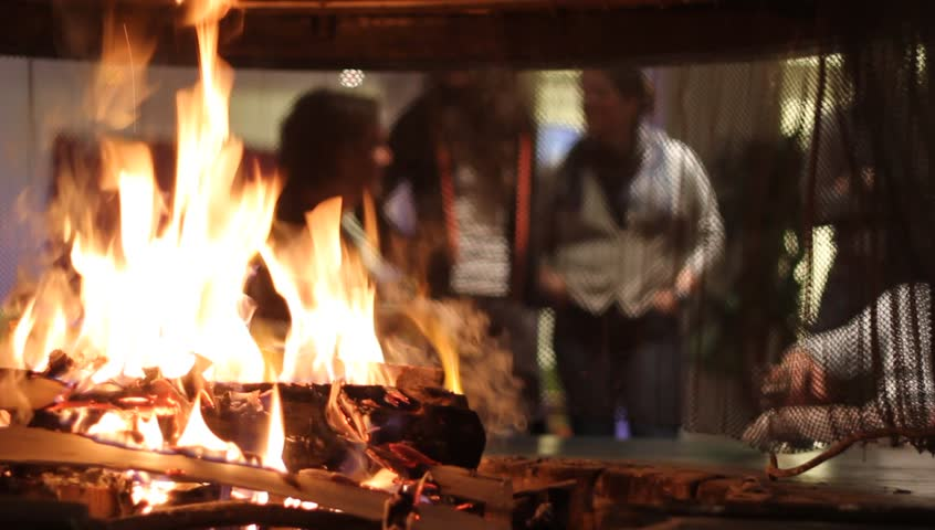 FLAINE, FRANCE - MARCH 26 : Focus on the fire the fireplace with the group of unrecognizable people on the blurred background. People are talking and drinking beer together on March 26th, 2015. | Shutterstock HD Video #9564653