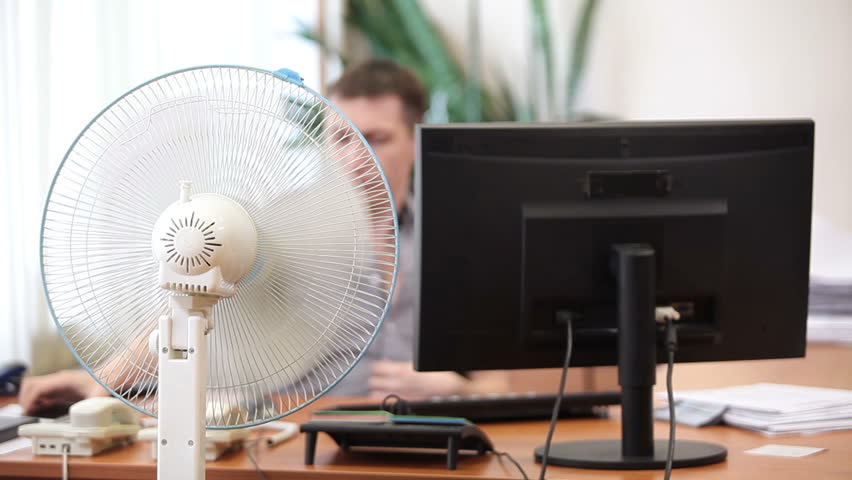 Office heat with cooling fan and perspiring white collar worker leaving his working place