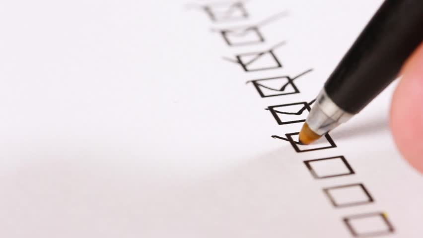 A person checking off a to do list. Check all the boxes of a checklist