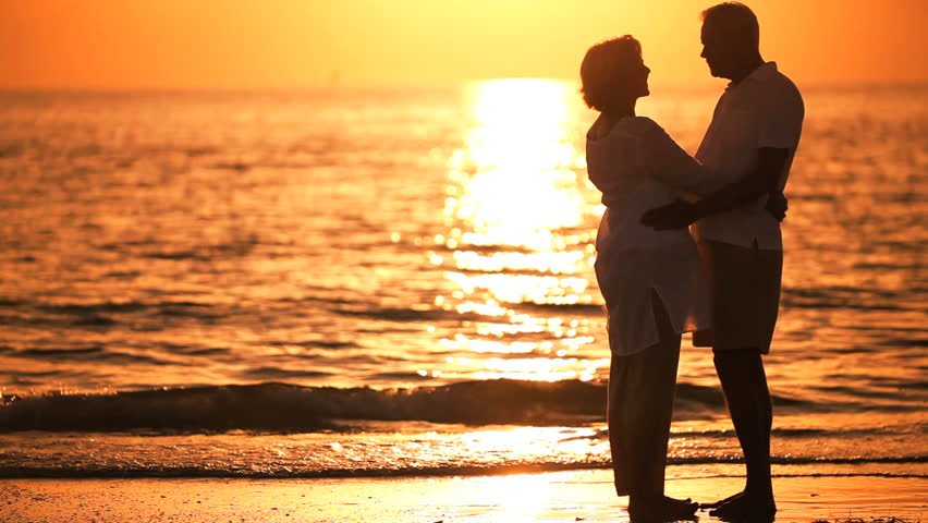 Healthy & affectionate senior couple enjoying a romantic sunset evening together on the beach | Shutterstock HD Video #966256