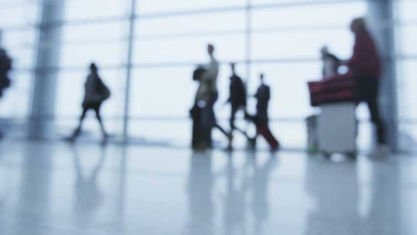 Silhouette people walking with luggage at airport terminal hall going on air plane travel. Many people walk with baggage. Out of focus blurry defocused. | Shutterstock HD Video #9666296