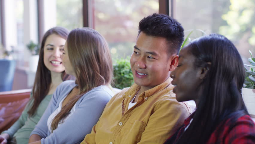 4K Happy group of young friends hanging out together at home. 1 young man turns to smile at camera. | Shutterstock HD Video #9670490