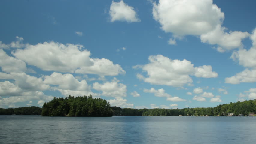 Summer lake with time-lapse clouds. This clip was assembled from a series of high resolution stills using a Canon 550D. Muskoka, Ontario, Canada.