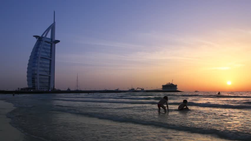 DUBAI - APRIL 17: Children playing on the beach near the Burj Al Arab, five-star hotel, at sunset on April 17, 2010 in Dubai, United Arab Emirates. At 321 m (1,053 ft), the Burj Al Arab is the fourth tallest hotel in the world.
