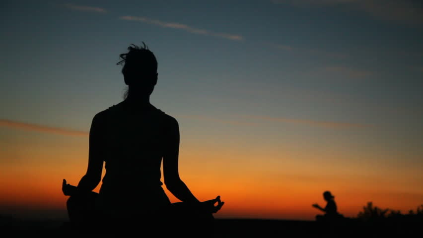 Silhouette of a girl meditating in the sunset. camera movement pan let to right   Shutterstock HD Video #9695468