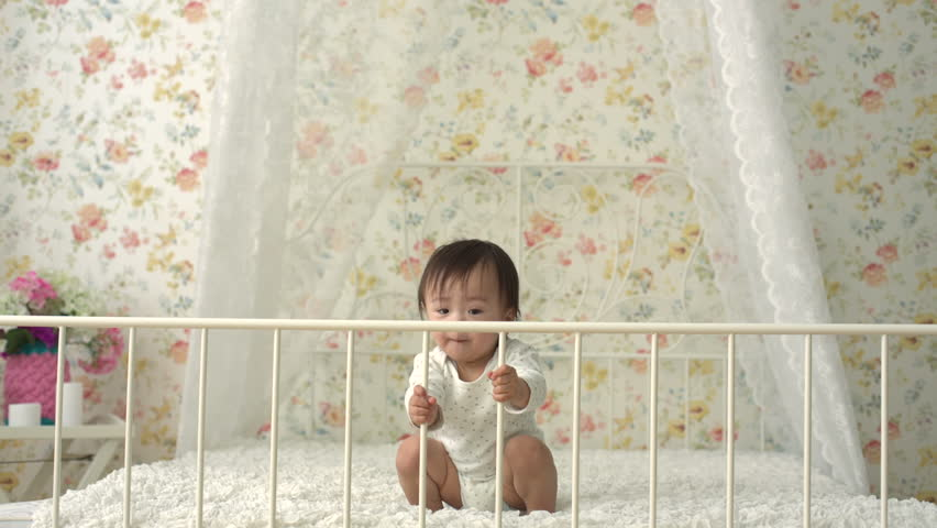 cute funny asian baby dancing on the bed