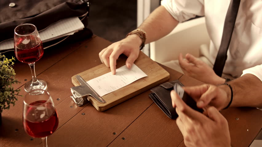 Waiter in a restaurant brings a credit card reader to the table for the bill to be paid.  Royalty-Free Stock Footage #9704456