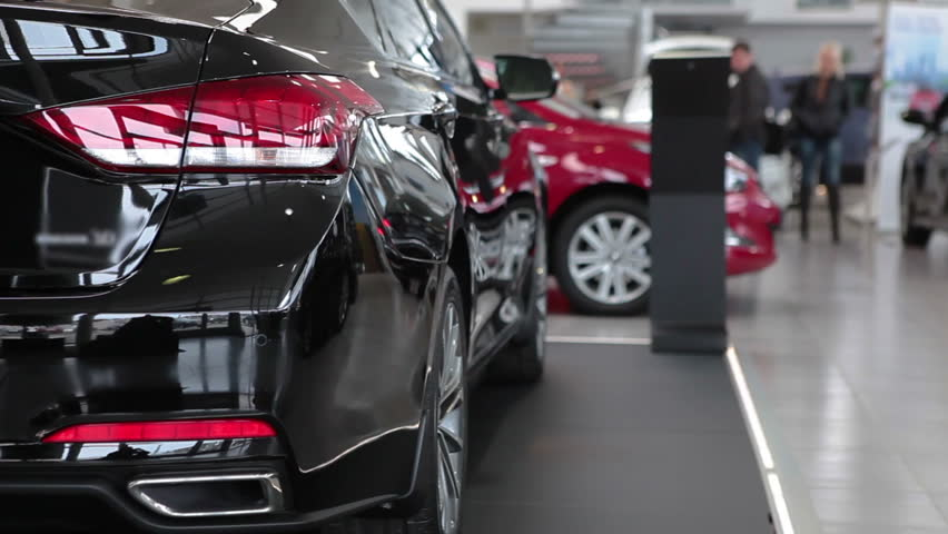 Luxury car dealership showroom with customers and salesmen. | Shutterstock HD Video #9711944