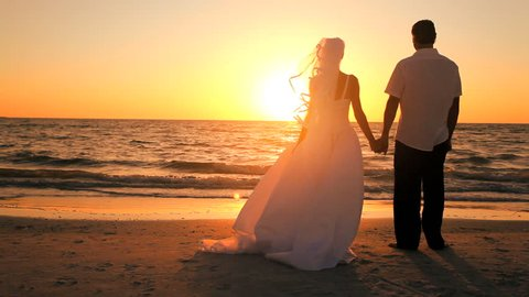 Attractive couple celebrate their wedding on a beautiful sandy beach at sunset