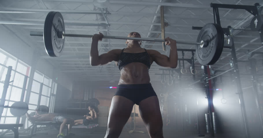 Medium shot slow mo tilt-down tilt-up men and women exercising and lifting weights female bodybuilder champion athlete doing power clean in cross fit gym | Shutterstock HD Video #9760700
