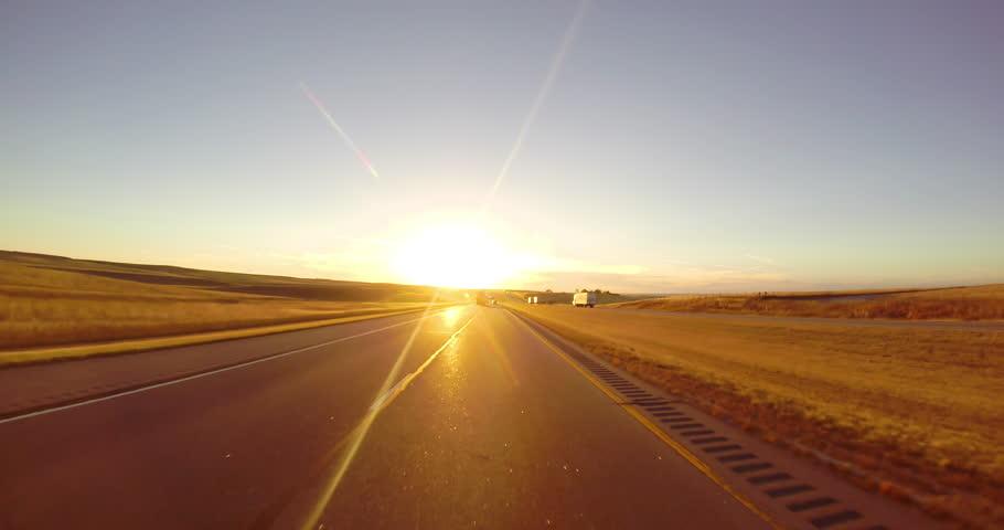 Driving down a highway at sunset along wheat fields | Shutterstock HD Video #9764600