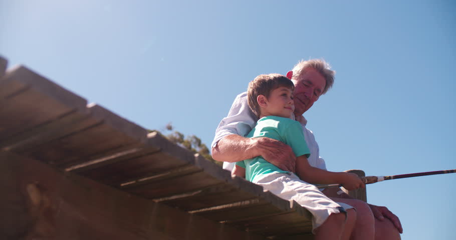 Retired grandfather sitting on a jetty teaching his grandson to fish, Panning in Slow Motion