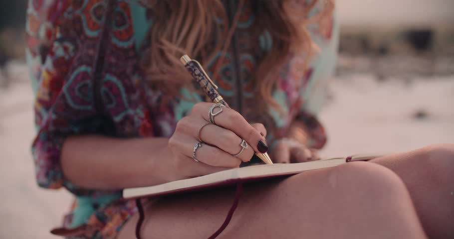 Cropped shot of a boho girl wearing a floral dress writing in her diary