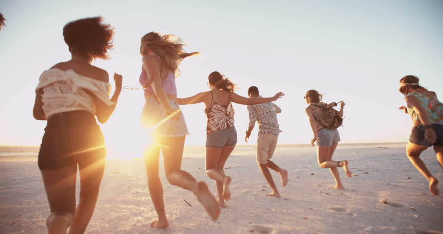 Group of young friends running in Slow Motion together on a beach at the water's edge at sunset | Shutterstock HD Video #9773921