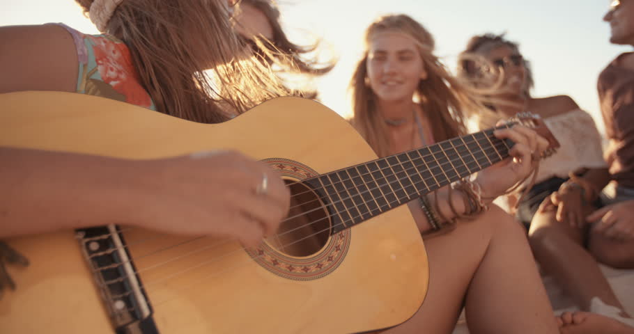 Girl playing her guitar for her friends at a beachparty on a summer evening in Slow Motion