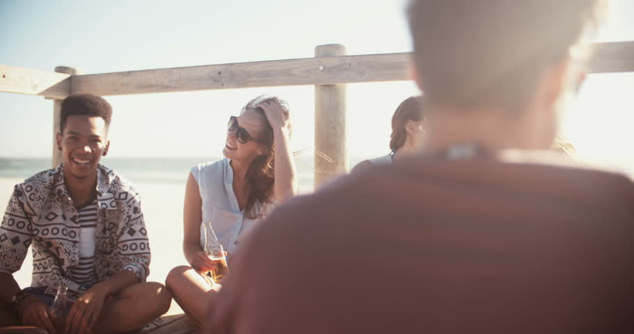Group of friends talking, relaxing and drinking beer together in summertime at the beach in slow motion, panning