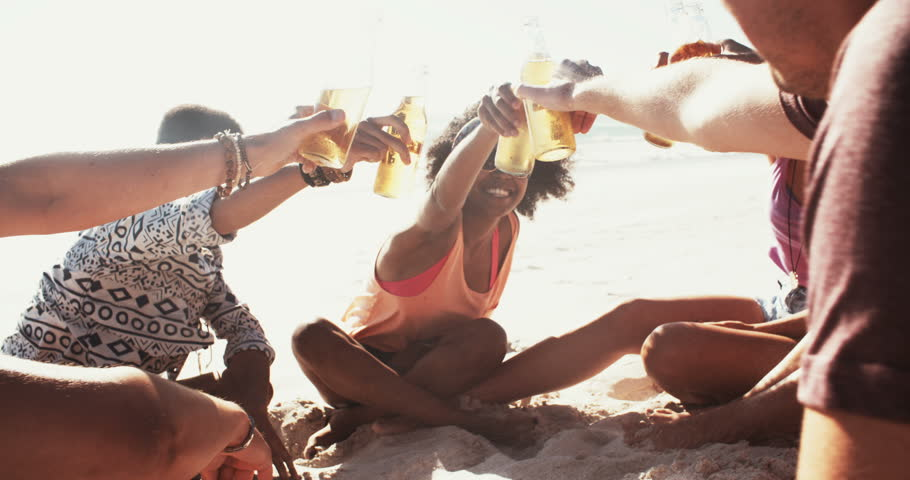 High angle shot of mixed racial group of friends having a beach party on a summer day saying cheers with beer in slow motion
