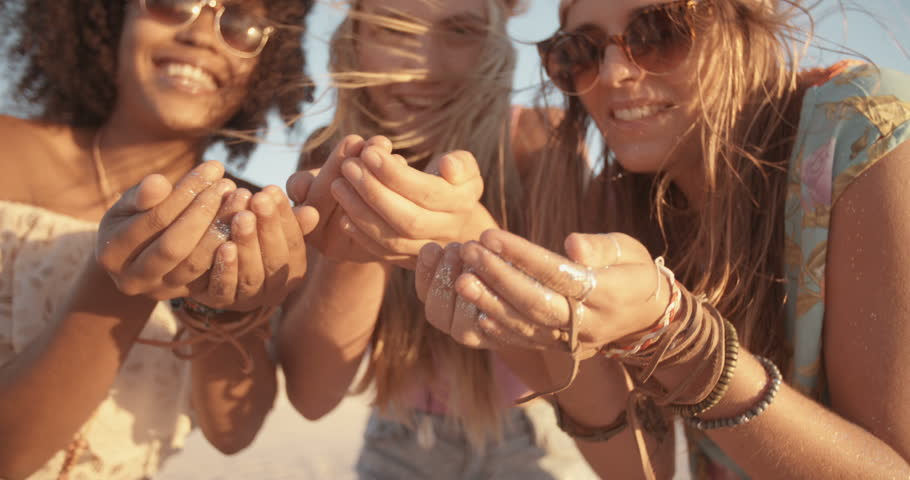 Mixed race group of girls blowing colorful confetti from their hands happily on a beach at sunset in Slow Motion