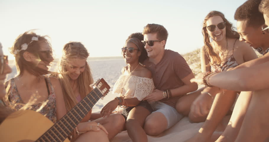 Group of friends relaxing at a sunset beachparty with someone playing a guitar in Slow Motion