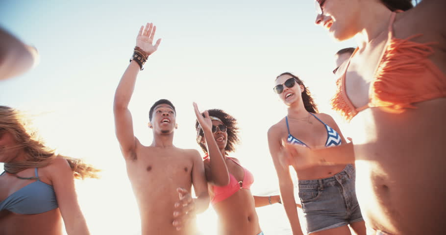 Group of mixed race friends having fun and giving each other high fives on a summer evening at the beach in Slow Motion