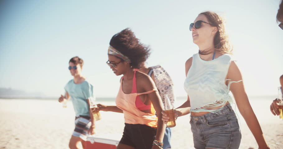 Group of friends walking on a beach and carrying a cooler box full of drinks for a party in slow motion, panning