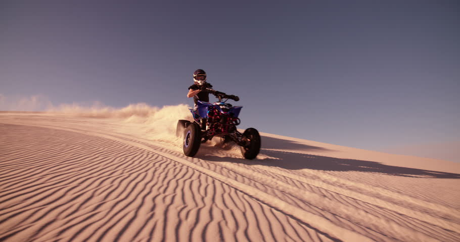 Competitive quad bike racer kicking up sand and dust while travelling up a sand dune, Panning in Slow Motion