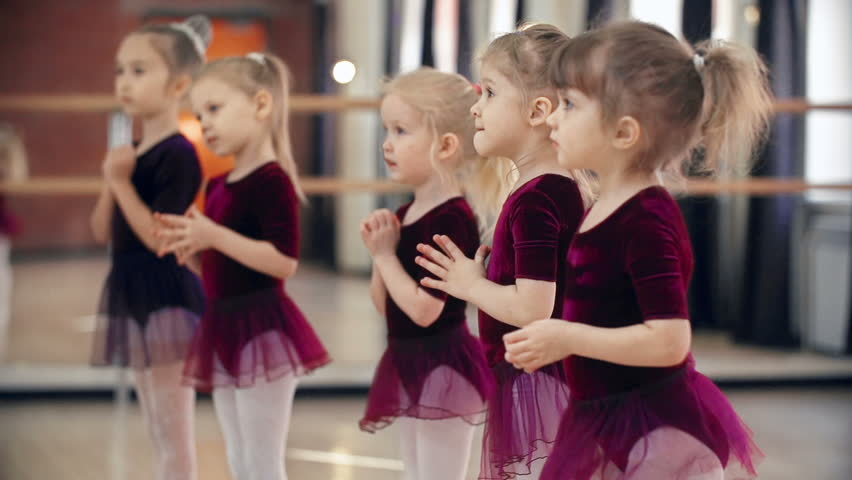 Little girls in ballet classroom moving at sixes and sevens