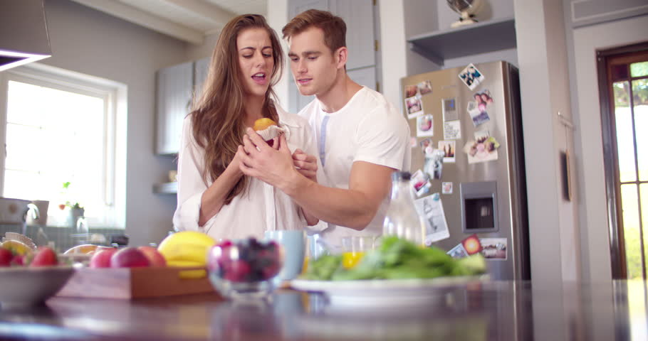 Cheeky boyfriend stealing a bite of his girlfriend's muffin in the kitchen early in the morning in Slow Motion #9791387