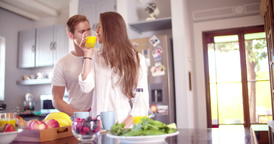 Loving guy hugging his smiling girlfriend in their kitchen early in the morning with breakfast being made in Slow Motion