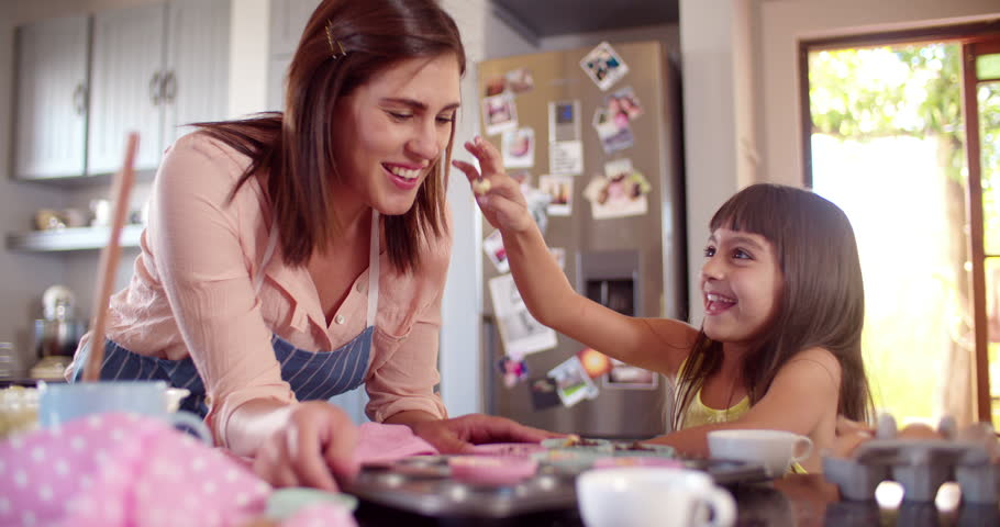 Laughing mom and daughter having fun together with the cupcake dough they are making in the kitchen while baking in Slow Motion
