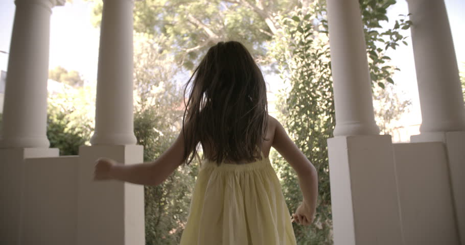 Rearview of a little girl running happily towards an open front door with vintage feel, Panning in Slow Motion #9791717