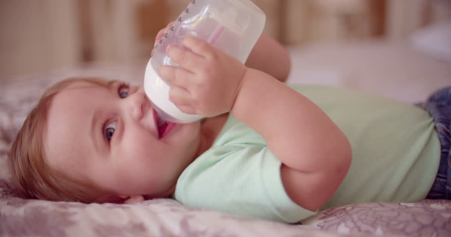 Smiling baby boy lying down while drinking milk from a bottle