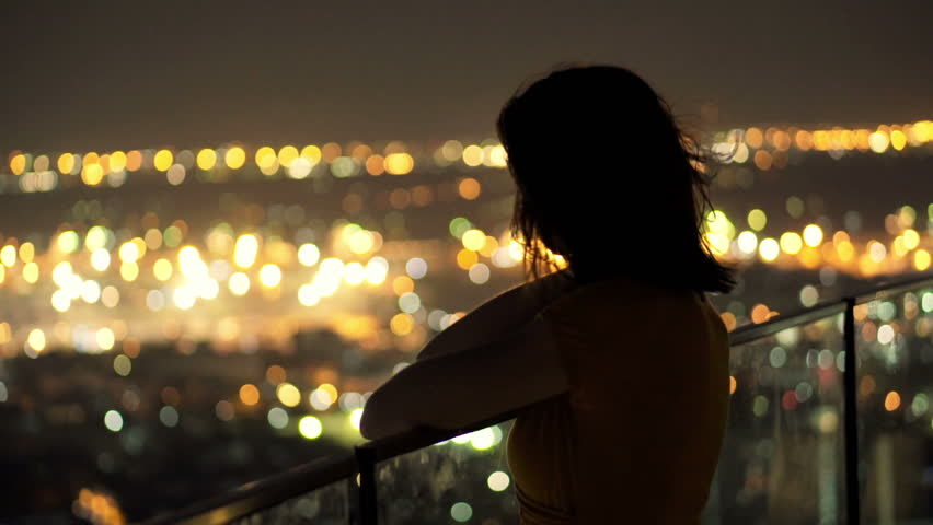 Young pensive woman looking at cityscape in the evening lights  | Shutterstock HD Video #9792812