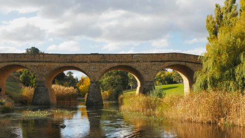 a sunny autumn view of the historic old stone bridge in richmond, tasmania, the oldest bridge still being used in australia
